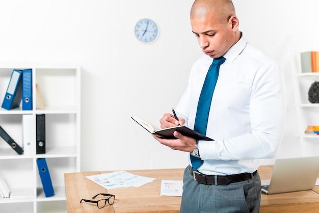 Gros plan, homme affaires, debout, devant, table, écrire, journal intime, à, stylo Photo gratuit