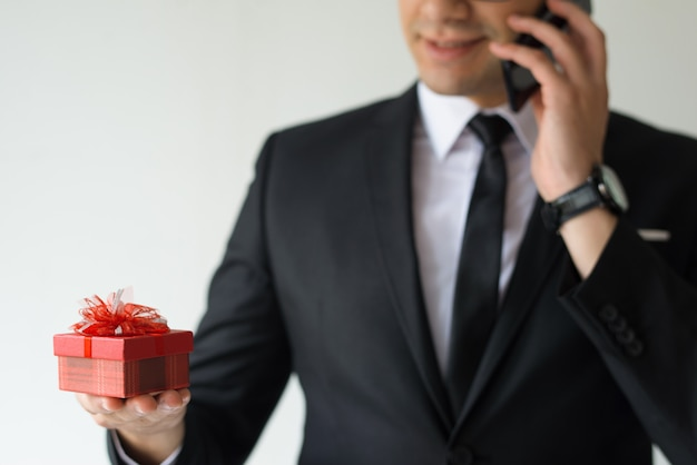 Gros plan d'un homme d'affaires détenant une boîte-cadeau et parler au téléphone Photo gratuit