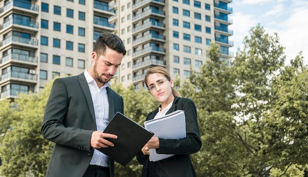 Gros plan, de, homme affaires, et, femme affaires, tenue, documents, debout, devant, bâtiment Photo gratuit