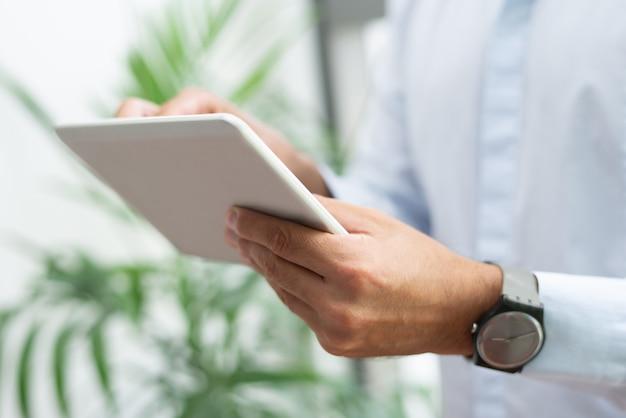Gros plan d'un homme d'affaires avec une montre-bracelet à l'aide d'une tablette Photo gratuit