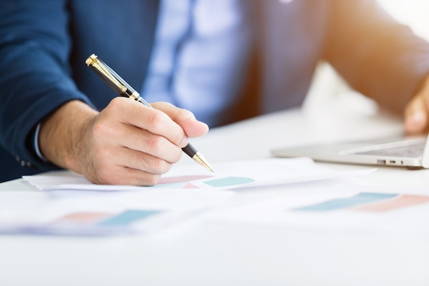 Gros plan, de, homme affaires, travailler, noter, papier affaires, et, main, clavier dactylographie, sur, ordinateur portable, dans, bureau Photo Premium