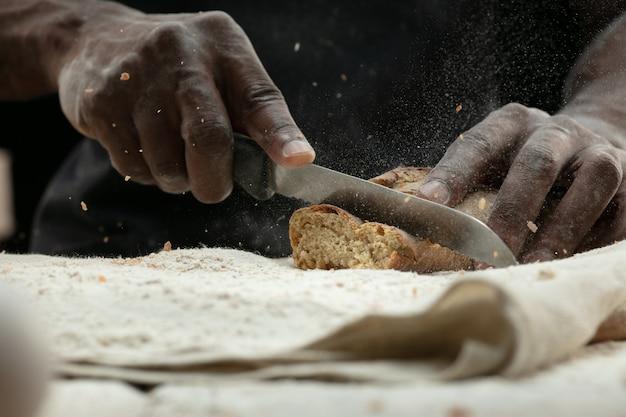 Gros Plan De L'homme Afro-américain Tranches De Pain Frais Avec Un Couteau De Cuisine Photo gratuit