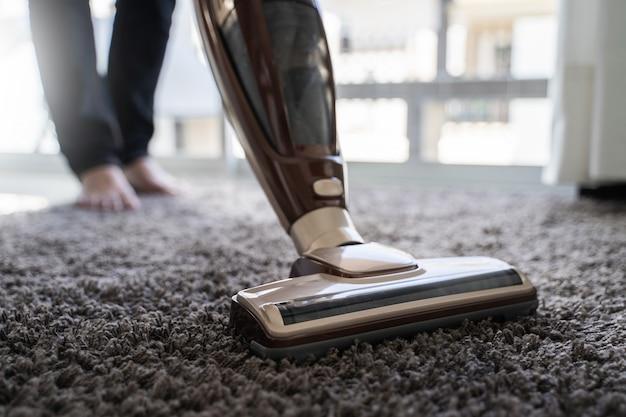 Gros plan homme à l'aide d'un aspirateur lors du nettoyage dans la chambre Photo Premium