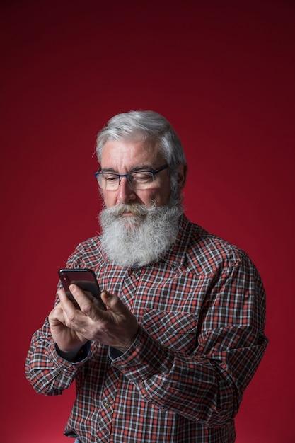 Gros plan, homme aîné, barbe grise, utilisation, debout, téléphone portable, contre, fond rouge Photo gratuit