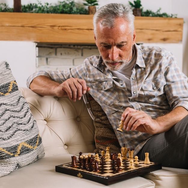 Gros plan, homme aîné, jouant aux échecs Photo gratuit