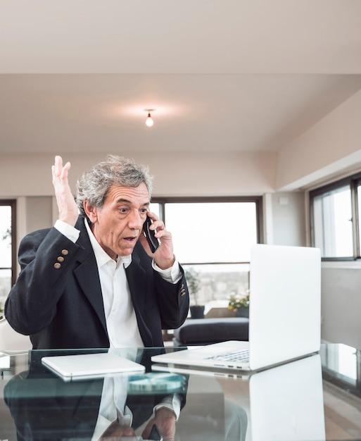 Gros plan, homme aîné, regarder, ordinateur portable, parler, sur, téléphone portable, dans, les, bureau Photo gratuit