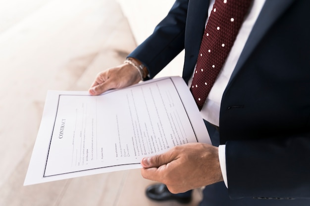 Gros plan d'un homme en costume tenant un contrat Photo gratuit