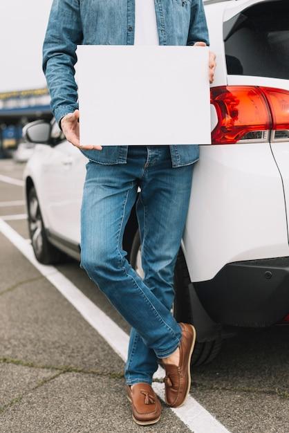 Gros plan d'un homme debout près de la voiture sur la route montrant une pancarte blanche vierge Photo gratuit