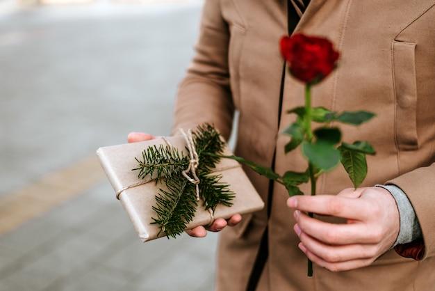 Gros plan d'un homme donnant une rose et un cadeau. la saint valentin. Photo Premium