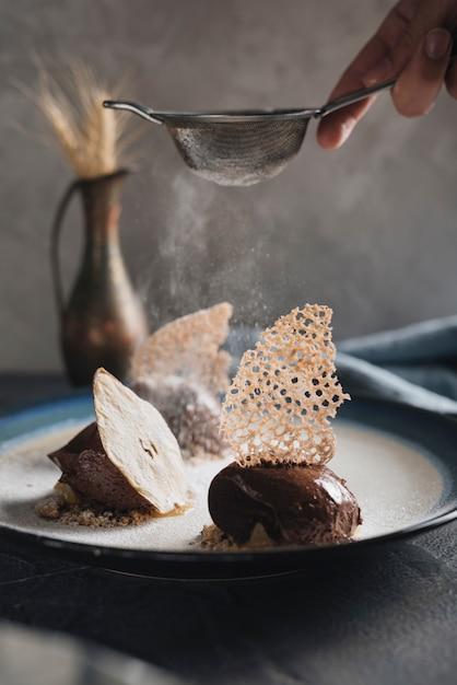 Gros plan, homme, épousseter, sucre, délicieux, pâtisserie chocolat Photo gratuit