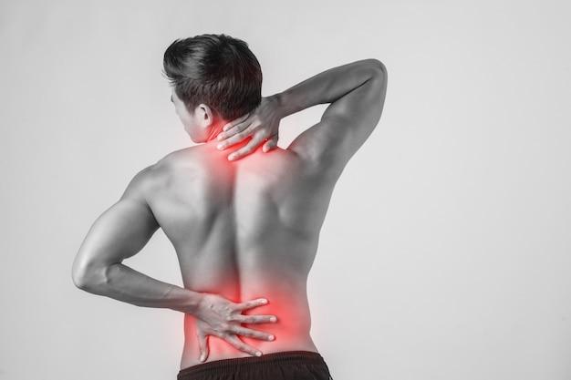 Gros plan de l'homme frottant son dos douloureux isolé sur fond blanc. Photo gratuit