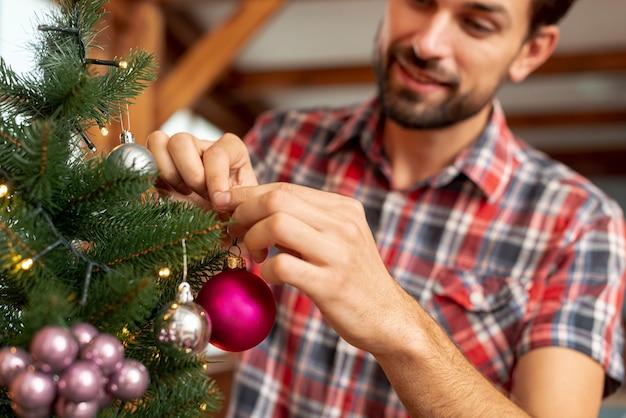 Gros plan homme heureux décorer le sapin Photo gratuit