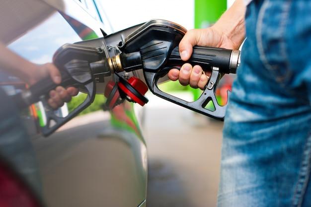 Gros plan d'un homme main ravitaillement en voiture à la station d'essence Photo Premium