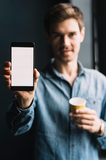 Gros plan d'un homme montrant un téléphone portable avec un écran blanc Photo gratuit
