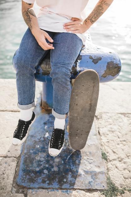 Gros plan, de, homme, pieds, à, skateboard, séance, sur, bollard Photo gratuit