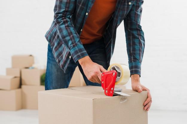 Gros plan d'un homme scellant une boîte en carton avec du ruban adhésif Photo gratuit