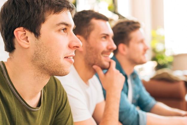 Gros plan, homme, séance, amis, regarder, télévision Photo gratuit