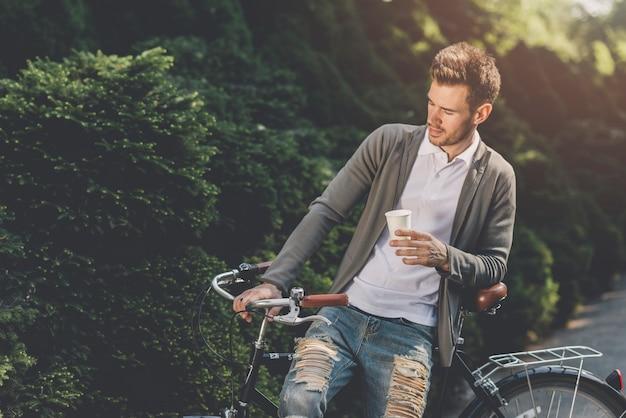Gros plan, homme, séance vélo, à, jetable, café, tasse Photo gratuit