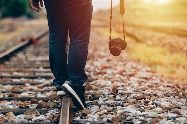 Gros plan d'un homme tenant une caméra numérique à pied dans le train Photo Premium