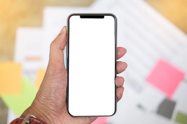 Gros plan d'un homme tenant un smartphone avec un ordinateur portable et un ordinateur portable à écran blanc au café. Photo Premium