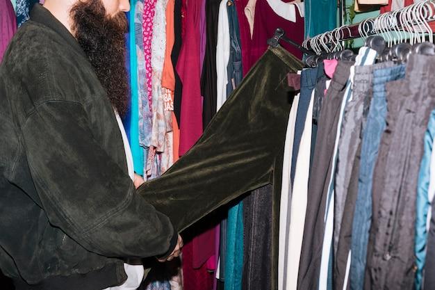 Gros plan, homme, tenue, noir, jean, pendre, rail, magasin Photo gratuit