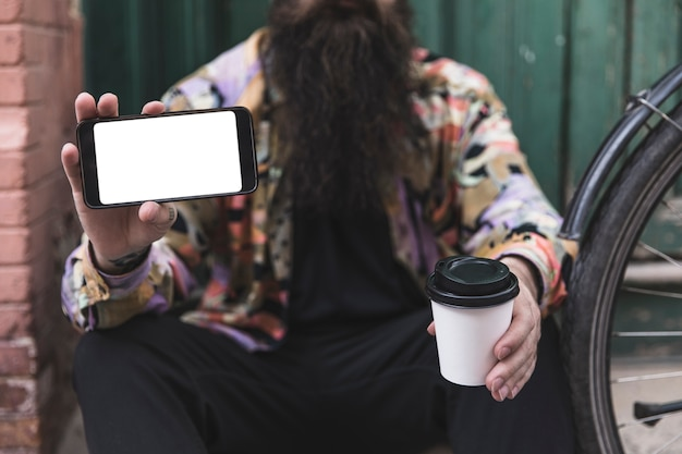 Gros plan, de, homme, tenue, téléphone portable, et, tasse à café jetable, dans main Photo gratuit