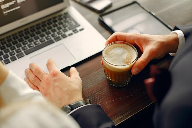 Gros plan homme travaillant avec un ordinateur portable à la table Photo gratuit