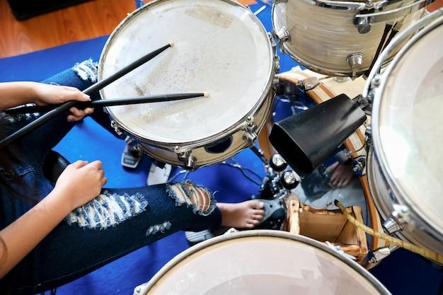 Gros plan des images de fille jouant du tambour. Photo Premium