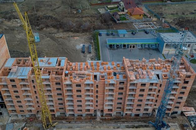 Gros Plan Sur Un Immeuble Résidentiel à Plusieurs étages En Construction En Brique Rouge Avec Une Partie D'une Grue. Photo Premium