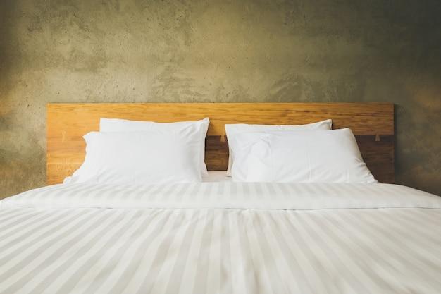 Gros plan intérieur de la suite chambre avec coussins blancs et fond de béton mur Photo Premium