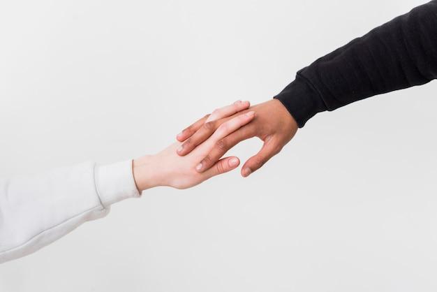 Gros plan, interracial, couple, tenue, l'autre, mains, contre, fond blanc Photo gratuit