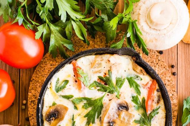 Gros plan, italien, frittata, tomates, champignons, persil, table bois vue de dessus Photo Premium
