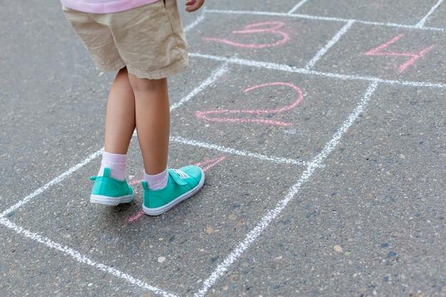 Gros plan sur les jambes et les classiques de childs peints sur asphalte. Photo Premium