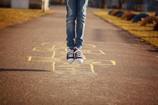 Gros plan des jambes du garçon et jouer à la marelle sur l'aire de jeux en plein air. jeu de rue populaire de la marelle Photo Premium