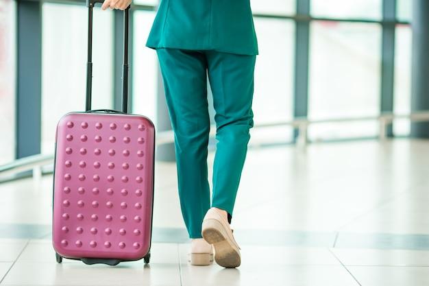 Gros plan jambes passager avion et bagages roses dans un salon d'aéroport va pour les avions de vol. Photo Premium