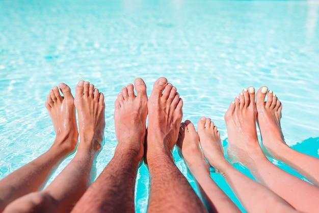 Gros plan des jambes de quatre personnes au bord de la piscine Photo Premium