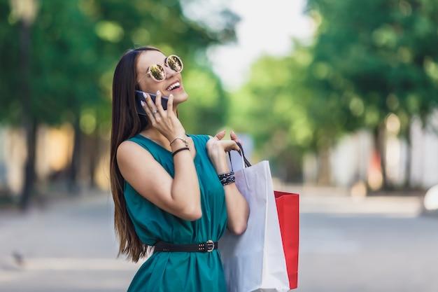 Gros plan, jeune, charmant, caucasien, cheveux, femme, à, sacs provisions, sourire, dents, et, parler téléphone Photo Premium