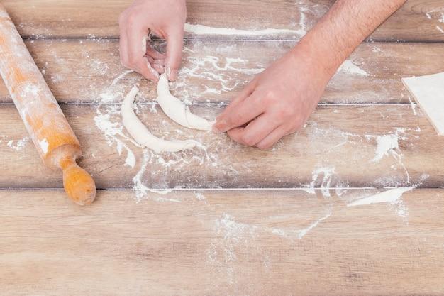 Gros plan, de, jeune, chef pâtissier, faire, croissant, sur, les, table Photo gratuit
