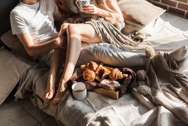 Gros plan, jeune, couple, délassant, lit, petit déjeuner, plateau bois Photo gratuit