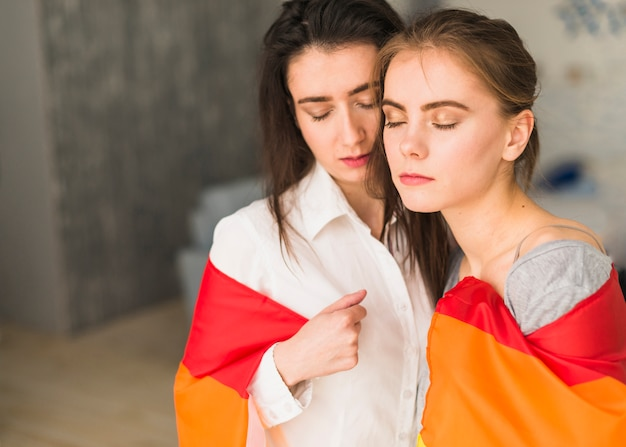 Gros plan, de, jeune, couple lesbien, emballer, dans, un, arc-en-ciel, drapeau, fermer, elle, yeux Photo gratuit