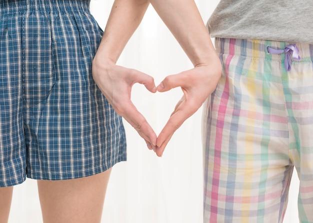 Gros plan, de, jeune couple lesbien, faire coeur, à, leurs, mains, isolé, sur, blanc, fond Photo gratuit