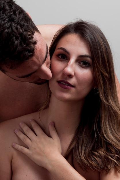 Gros plan jeune couple nu s'embrasser Photo gratuit