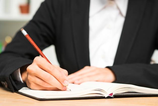 Gros plan, jeune, femme affaires, écrire, crayon rouge, journal Photo gratuit