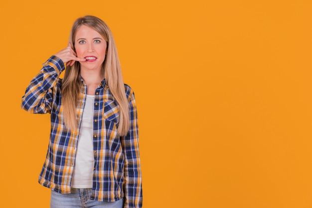 Gros plan, jeune, femme, appel, geste, fond orange Photo gratuit