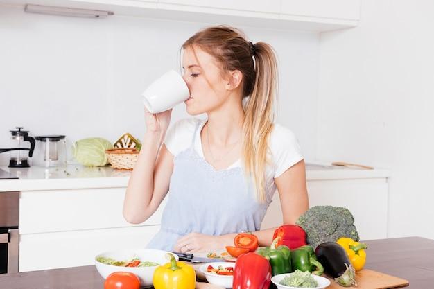 Gros plan, de, a, jeune femme, boire café, à, coloré, frais, legumes, sur, table bois Photo gratuit