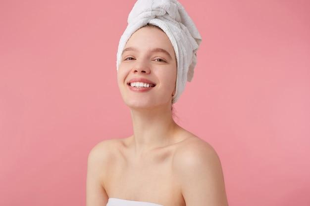 Gros Plan D'une Jeune Femme Joyeuse Après Spa Avec Une Serviette Sur La Tête, Sourit Largement, A L'air Heureux Et Apprécié, Se Dresse. Photo gratuit