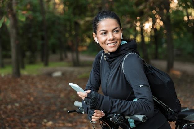 Gros Plan D'une Jeune Femme Joyeuse De Remise En Forme à Cheval Sur Un Vélo Dans Le Parc, écoutant De La Musique Avec Des écouteurs, Tenant Un Téléphone Mobile Photo Premium