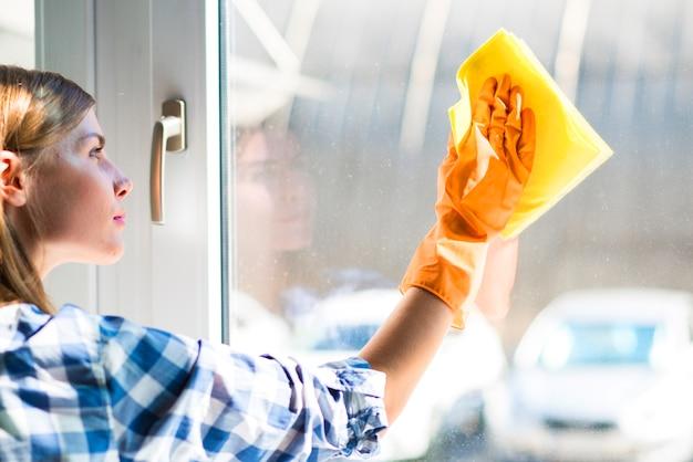 Gros plan, de, jeune femme, lingettes, fenêtre, à, serviette jaune Photo gratuit