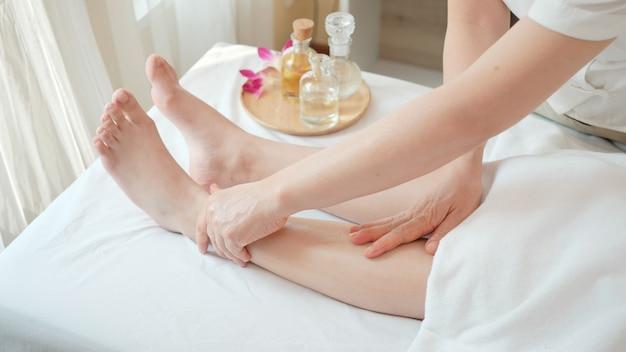 Gros Plan Jeune Femme Recevant Un Massage De Réflexologie Des Jambes Au Salon De Beauté Spa. Massage Pour La Santé Photo Premium