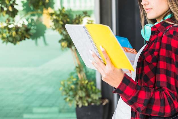 Gros plan d'une jeune femme souriante, lisant des livres à l'extérieur Photo gratuit